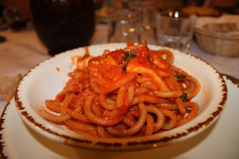 Pasta del Borgo (pasta fatta in casa con farina integrale e segale, condita con stocco, guanciale, pomodorini, basilico e peperoncino; servita a tavola con la ricotta affumicata di Mammola)
